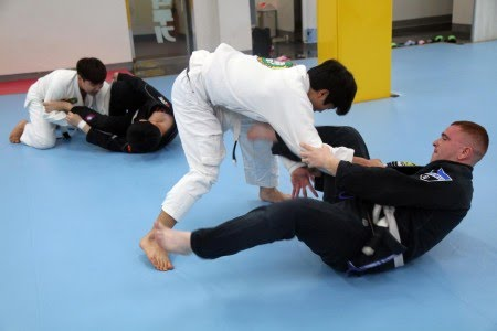 Pfc. Kaleb Whitten (right), an intelligence analyst with 19th Expeditionary Sustainment Command, and Onalaska, Texas native, tries to keep Ji Hoon Lee in his guard while practicing jiu jitsu at the Hoon Machado gym in Taegu, Korea, Jan. 29.